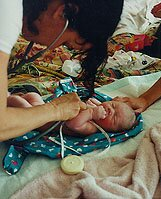 midwife checking newborn's heartbeat
